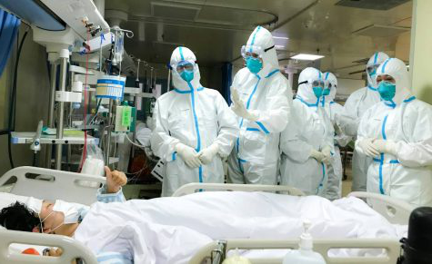 A coronavirus patient in Wuhan, China gives a thumbs up sign to a doctor